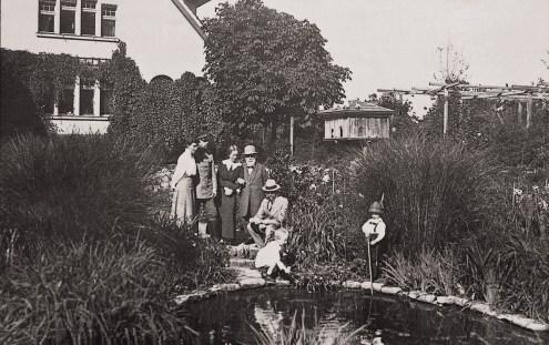 Karl Foerster mit Familie und Besucherkinder am Teich. Im Hintergrund das erste Taubenhaus. Foester. M.,2005: 12